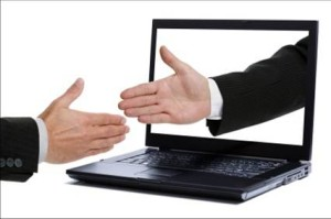 shaking hands over computer